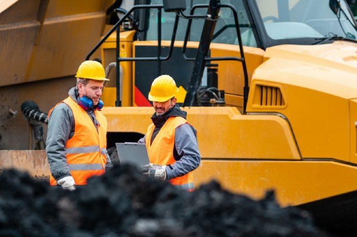 Vor einem schweren Kipplader stehen zwei Arbeiter mit Helmen und Warnwesten und besprechen etwas. Das Bild soll ausdrücken, wie wichtig Kommunikation im Kontext von Arbeitssicherheit und Arbeitsschutz ist.